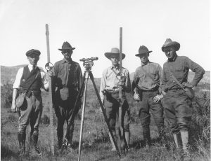 USGS topographic field party, circa 1925, with a Wye level on a tripod and two stadia rods.  Photo credit U.S. Geological Survey  Department of the Interior